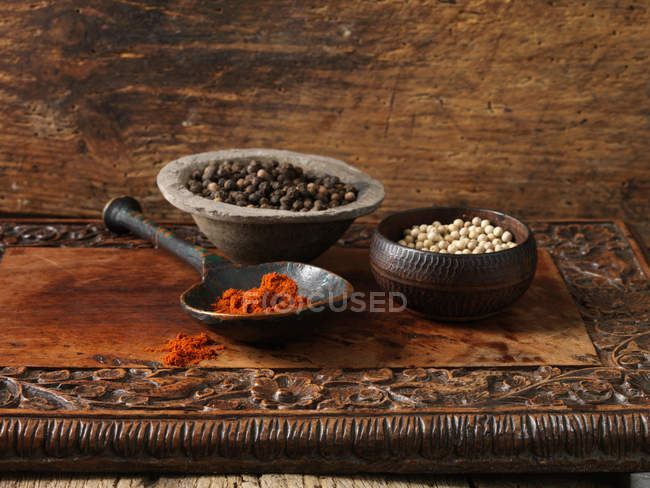 Black and white peppercorns and paprika — Stock Photo