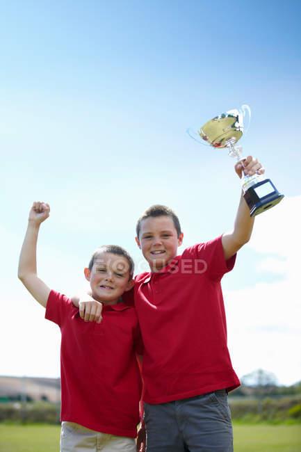 Мальчики радуются с трофеем на открытом воздухе, сосредоточиться на переднем плане — стоковое фото