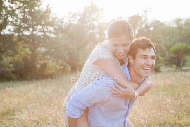 Feliz novio dando piggyback a la novia - foto de stock