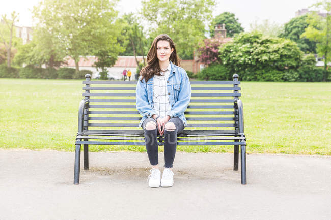Portrait of young woman sitting on park bench — Stock Photo
