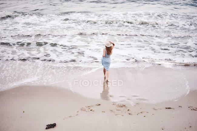 Chapeau femme marchant sur la plage — Photo de stock