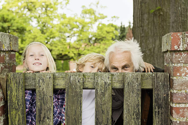 Grandfather and grandchildren peering over wooden gate — Stock Photo