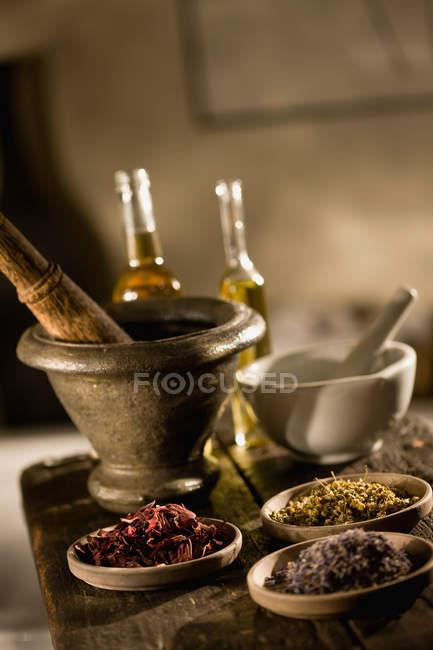 Ervas e óleos na tabela com bacias de mistura — Fotografia de Stock