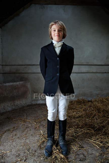 Мальчик, стоящий в одежде лошади в конюшне — стоковое фото