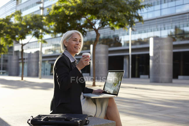 Businesswoman sitting outside using laptop and drinking hot drink — Stock Photo