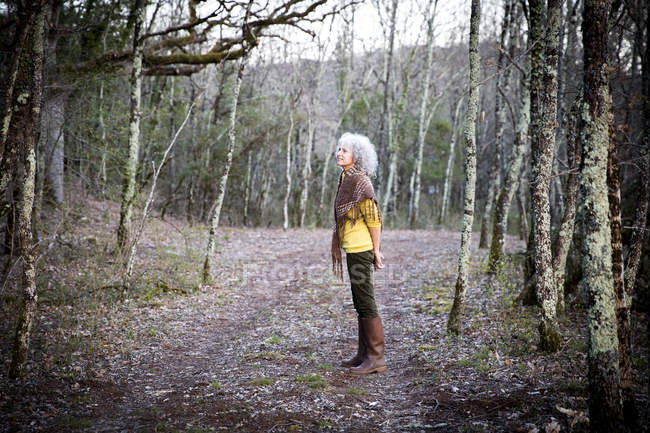Mature woman standing in woodland looking — Stock Photo