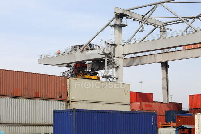 Container crane and stacks of freight containers — Stock Photo