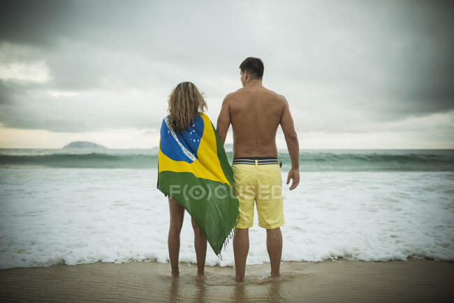 Young couple, woman wrapped in brazilian flag, Ipanema Beach, Rio de Janeiro, Brazil — Stock Photo