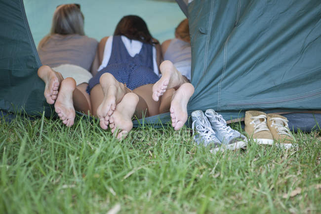 Three young females friends feet at tent entrance — Stock Photo