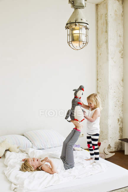 Little sisters playing with soft toy on the bed — Stock Photo