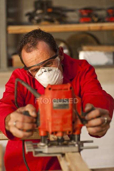 Carpenter working with power tools — Stock Photo