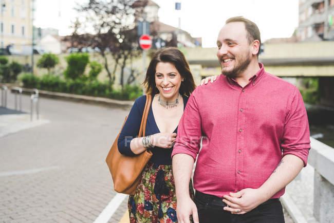 Couples heureux marchant sur le trottoir ensemble — Photo de stock
