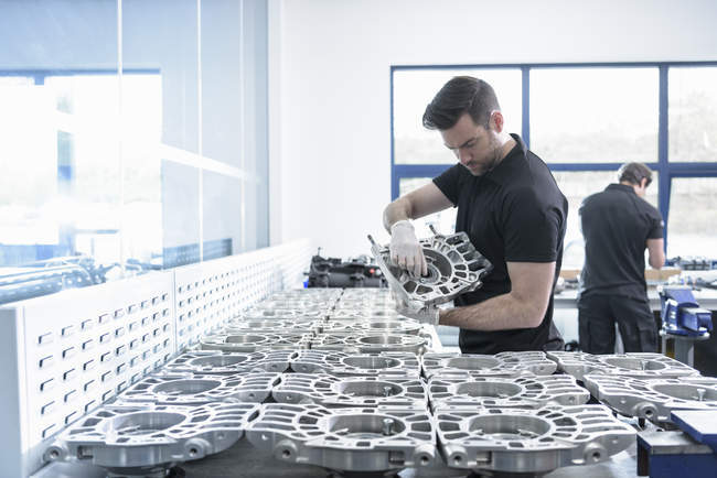 Engineer working on part in racing car factory — Stock Photo