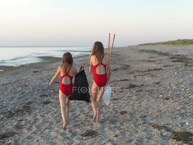 Девушки гуляют по песчаному пляжу — стоковое фото