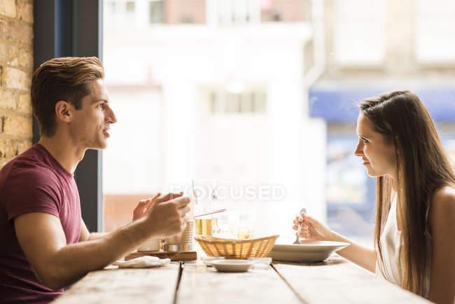 Jeune couple bavarder tout en mangeant au restaurant — Photo de stock