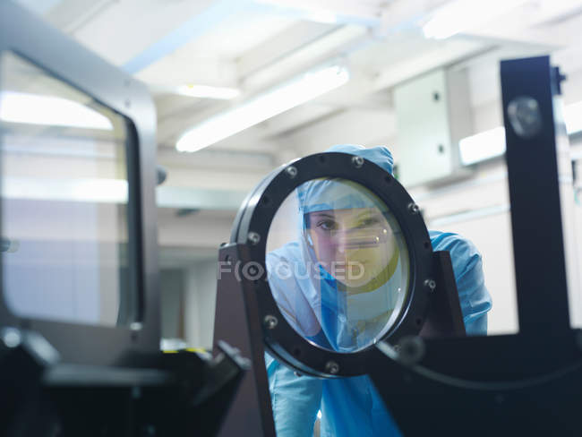 Female scientist in protective clothing checking a laser filter in a laboratory — Stock Photo
