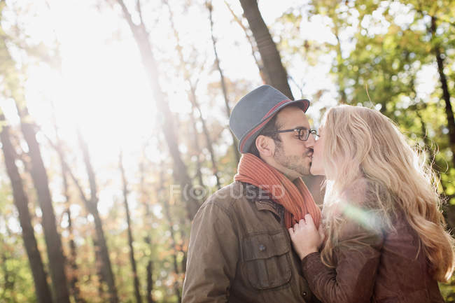 Sonriente pareja besándose en el bosque - foto de stock