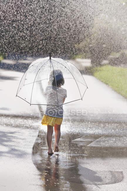 Vista trasera de chica descalza llevando paraguas caminando por el charco de la calle — Stock Photo