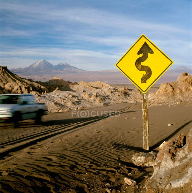 Curvy arrow on road sign at rural road with moving car — Stock Photo