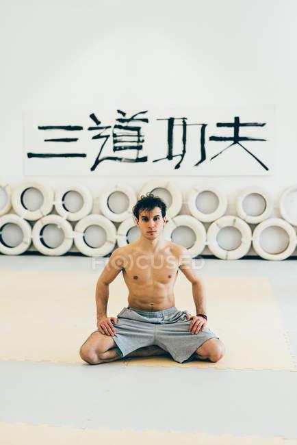 Mann kniet auf Gymnastikmatte Blick in die Kamera — Stockfoto