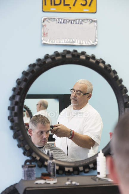 Barbier rasage cheveux client masculin dans le salon, réflexion dans le miroir rond — Photo de stock
