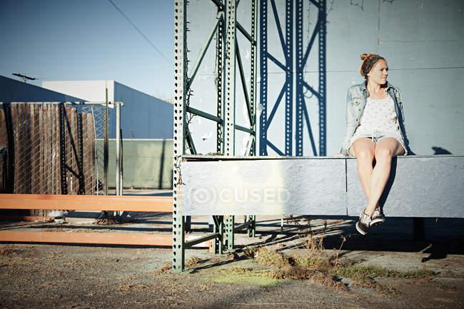 Жінка сидить на стіні в промисловому районі — стокове фото