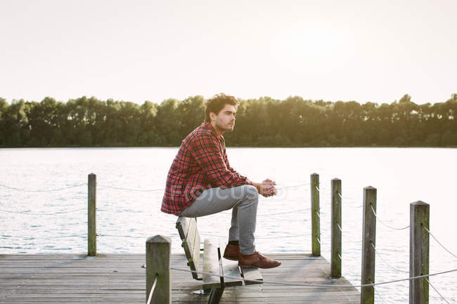 Young Man Sitting On Bench On Jetty Looking Across Water Side View