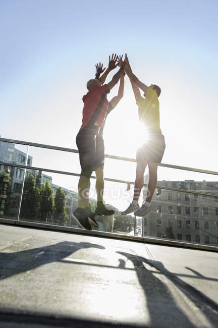Runners jumping doing high-five, Munich, Allemagne — Photo de stock