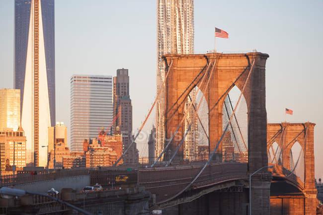 Мост в Нью-Йорке с флагом на вершине и горизонтом на закате — стоковое фото