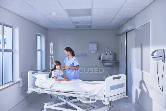 Nurse adjusting intravenous drip for girl patient in bed on hospital children's ward — Stockfoto
