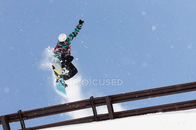 Snowboarder pulando sobre trilhos de metal — Fotografia de Stock