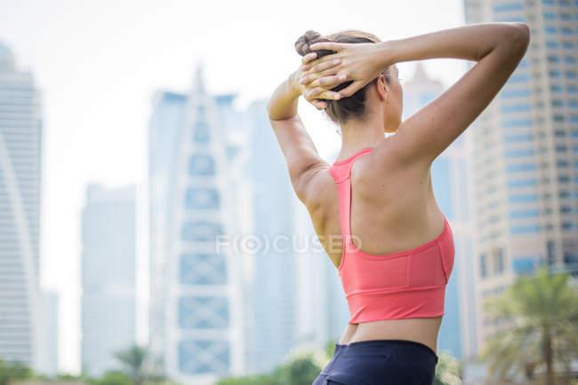 Жінка навчання, скручування з руки за голову в парку, Дубай, Об'єднані Арабські Емірати — стокове фото