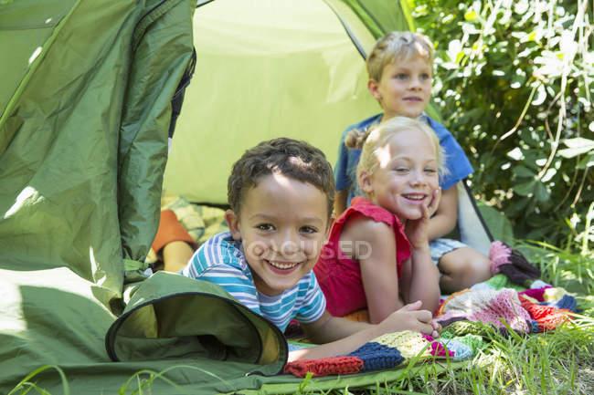 Portrait of three smiling children lying in garden tent — Stock Photo