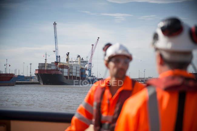 Тягачи на буксире с контейнерным судном на заднем плане — стоковое фото