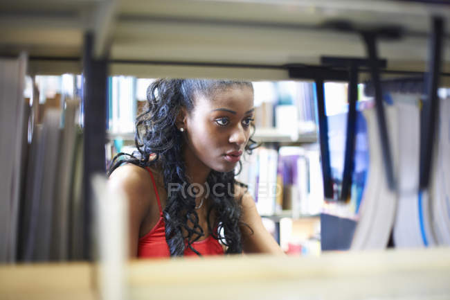Jeune étudiante à la recherche d'étagères de bibliothèque — Photo de stock