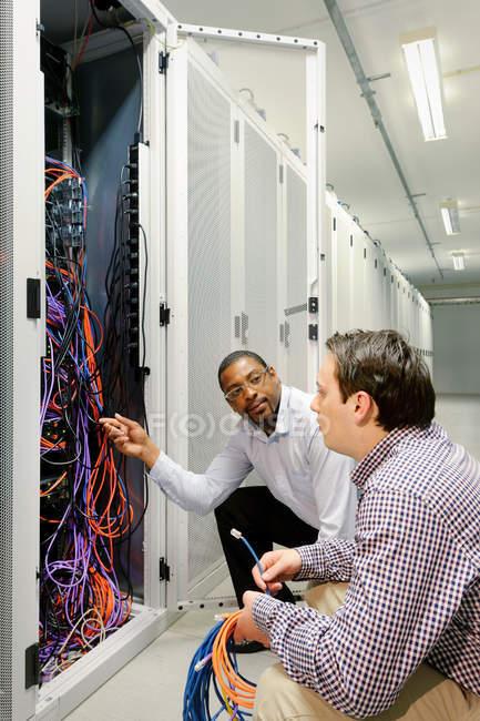 Підприємці, які вивчають дроти на сервері — стокове фото