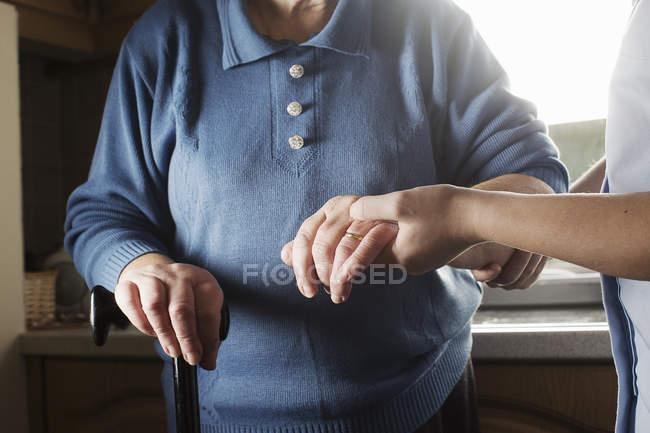 Assistente per la cura personale che sostiene la donna anziana a piedi — Foto stock