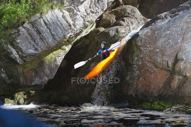 Mid adult man kayaking down river waterfall — Stock Photo