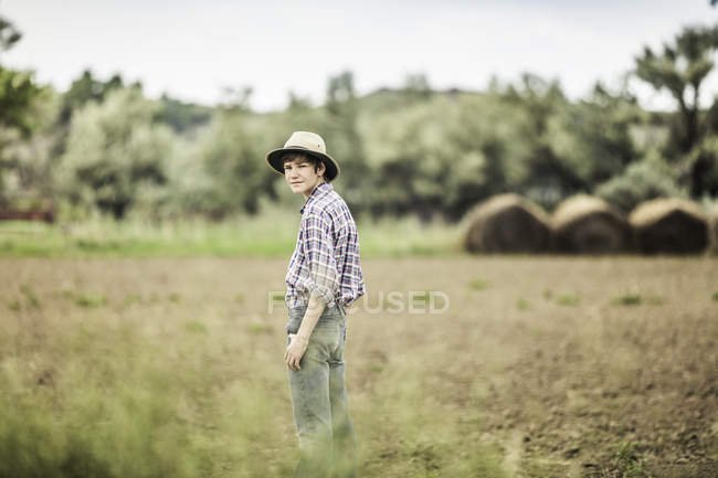 Teenage boy standing looking over his shoulder in ploughed field — Stock Photo