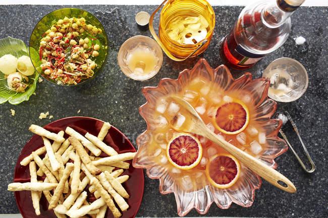 Ainda vida de tigela de coquetel de soco com batatas fritas e lanches — Fotografia de Stock