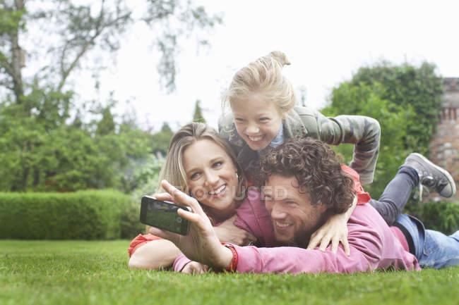 Pai fotografar família deitado no gramado — Fotografia de Stock