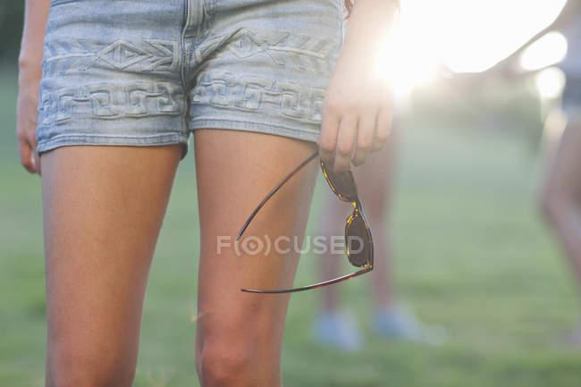 Image recadrée d'une jeune femme en short portant des lunettes de soleil — Photo de stock
