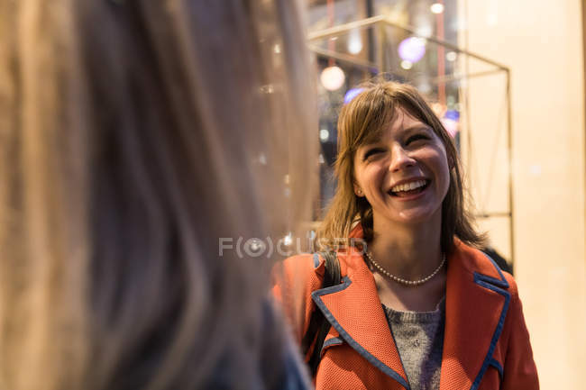 Two female friends having conversation outside shop — Stock Photo