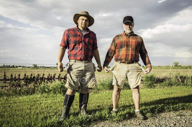 Попередня картина фермерів з кишенями всередині, які дивляться на камеру посміхаючись — стокове фото
