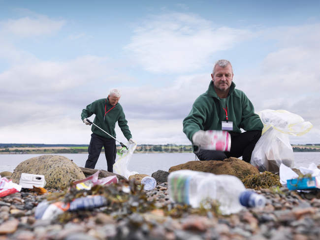 Two male environmentalists removing litter from seashore — Stock Photo