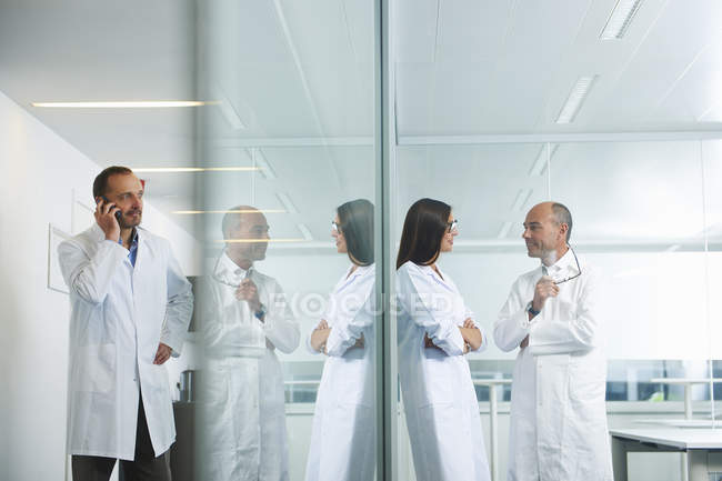 Male and female doctors chatting and talking on phone at office — Stock Photo