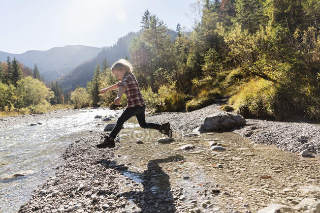 Little girl jumping mid air at riverside — Stock Photo