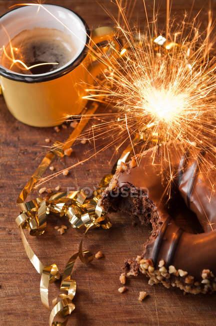 Bengala llameante con rosquilla y taza de café - foto de stock