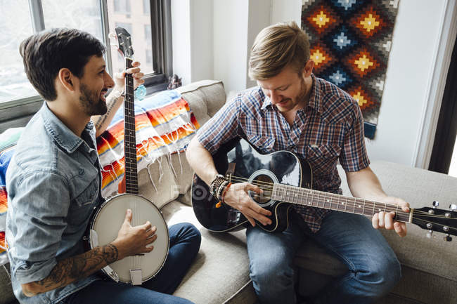 Male couple at home, play guitar and banjo, laughing — Stock Photo