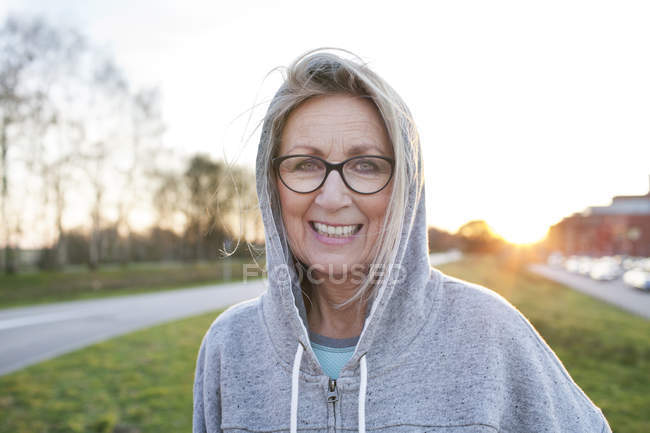 Portrait of woman wearing eyeglasses and hooded top looking at camera smiling — Stock Photo